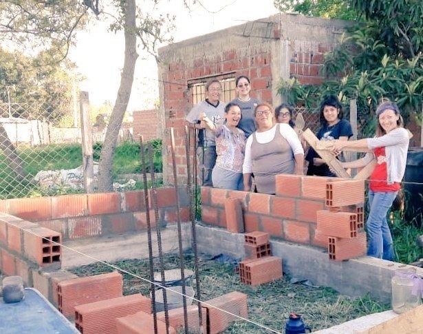 Mujeres posan frente a los encadenados y paredes que ellas mismas construyeron durante los talleres. Barrio 6 de Enero, Cuartel V, Moreno.