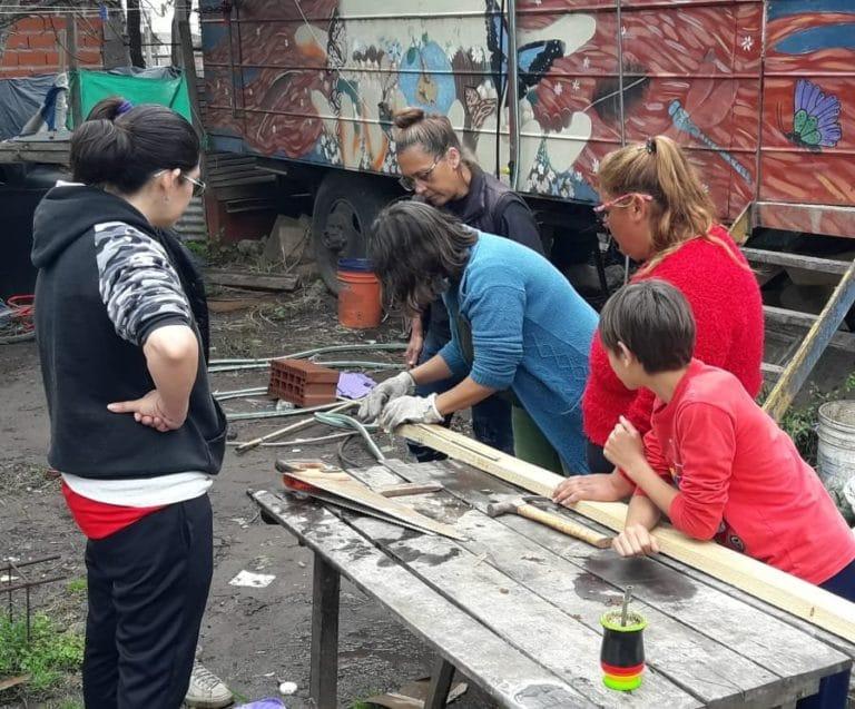 Mujeres del taller del Barrio 6 de Enero, preparando el encofrado. detrás, un camión casa, donde vive Mariana Canicova con sus hijos hasta terminar la construcción de su casa.