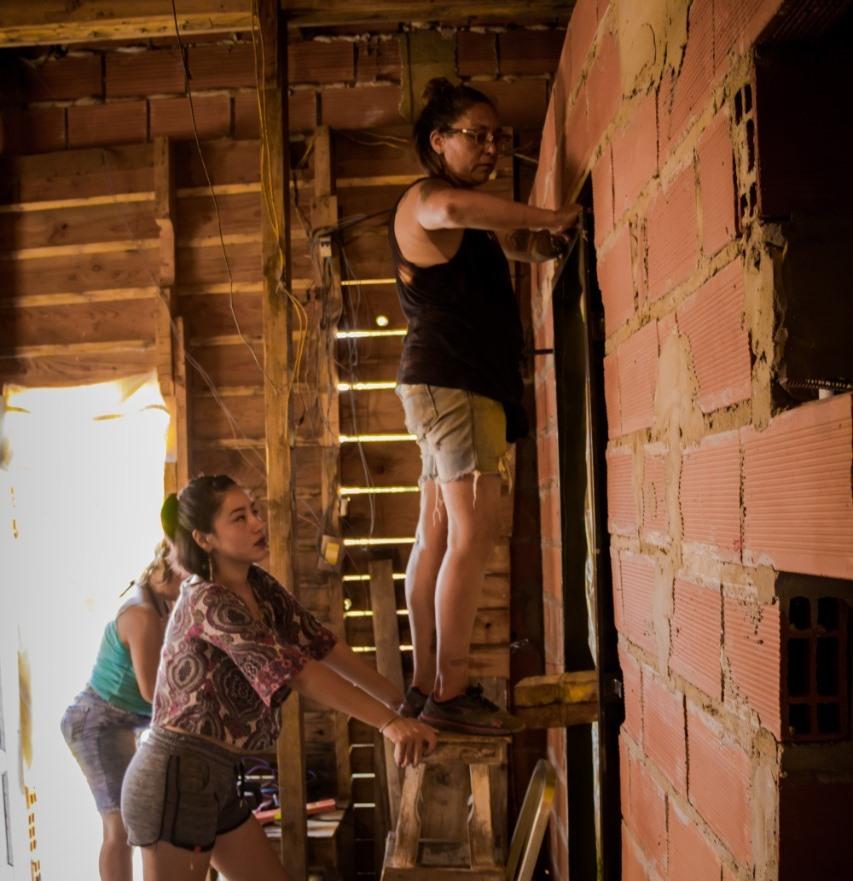Arriba la tallista presenta el marco de la puerta que estan colocando, debajo las Aprendices observan y participan de la actividad. Barrio 6 de Enero, Cuartel V, Moreno.
