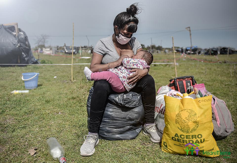 Toma de tierras en Guernica año 2020, provincia de Buenos Aires. Una mama amamanta a su bebe sentada en unas bolsas de consorsio  que son sus unicas pertenencias.