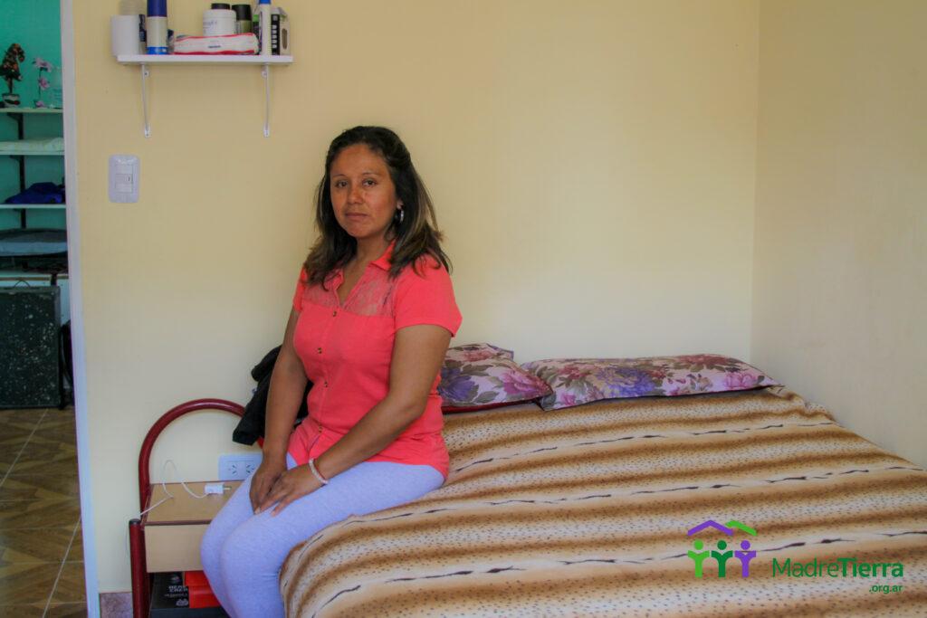 Angelica sentada en su cama, en su nueva Habitación.