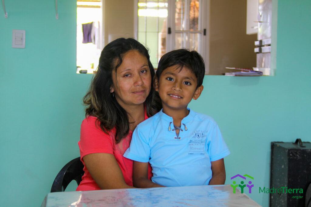 Angelica y su hijo sentados en le comedor de su casa recientemente construido.