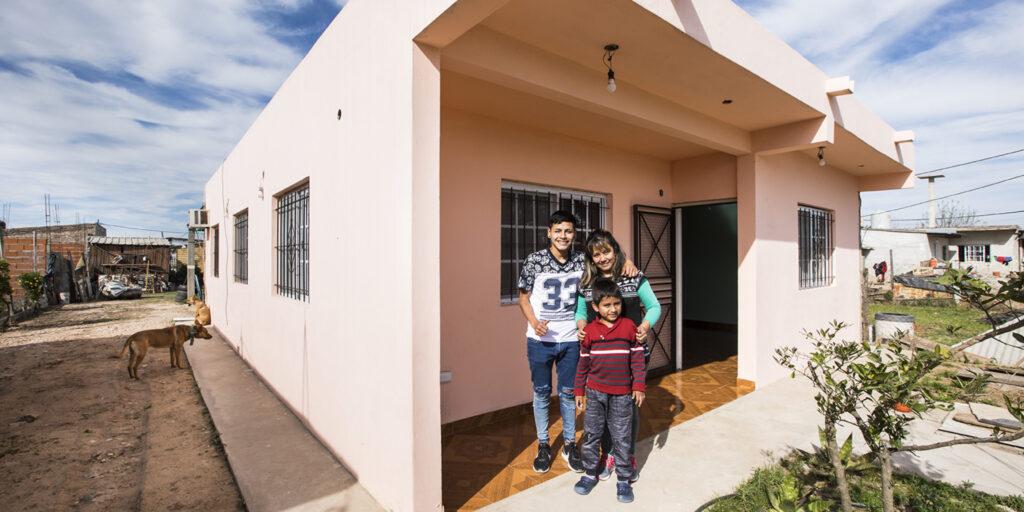 Angelica junto a sus hijos frente a su casa mejorada.